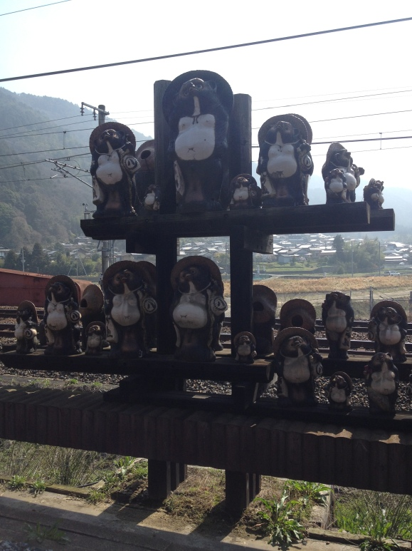 These were along the railroad tracks to Arashiyama. They are very popular in Kyoto and around Biwa Lake. According to our tour guide, these figures are Japanese raccoon dogs, or tanuki. Many storefronts have tanukis because of the specific features these characters hold: 1) The hat it wears represents the business's readiness to protect against trouble or bad weather.  2) The big eyes is to help perceive the environment and help make good decisions. 3) It holds a sake bottle that represents virtue.  4) A big tail is a means to provide steadiness and strength until success is achieved. 5) An over-sized scrotum symbolizes financial luck (yeah, not sure how that came about...) 6) A promissory note that represents trust or confidence. 7) A big belly that symbolizes bold and calm decisiveness 8) A friendly smile (because being happy never killed anyone)