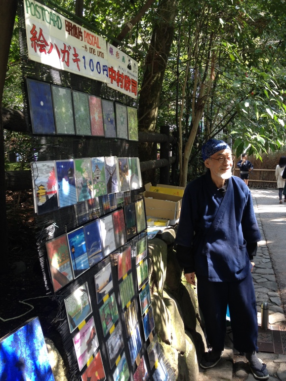 The man next to the dragonfly craftsmen was selling postcard prints of his paintings.